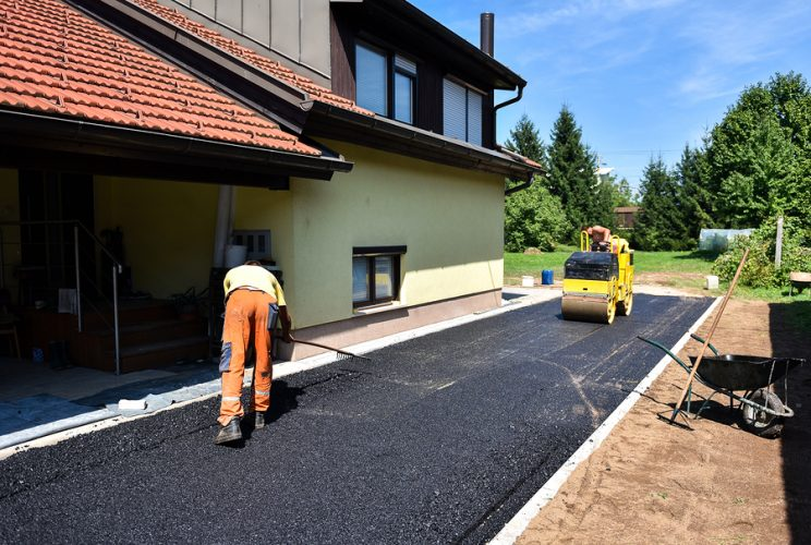 Worker with Tool and Asphalt Roller